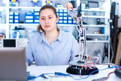 Girl in robotics laboratory. Young woman technician repair roboter manipulator Kuvituskuvat