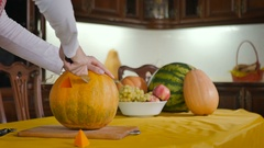 The girl carves the pumpkin on the Halloween Stock Footage