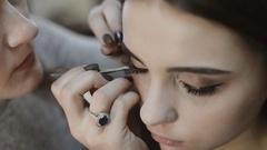 Makeup artist applying false eyelashes to model's eyes Stock Footage