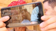 Tourist taking selfie with a indian senior with a mustache, Rajasthan Stock Footage