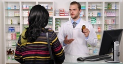 Pharmacist Man Talk Woman Patient and Explain on Drug Bottle Recipient Pharmacy Stock Footage