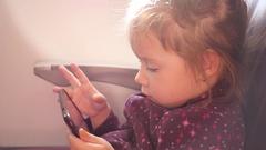 Kid girl passenger watch slide type smart phone display in a plane during flight Stock Footage
