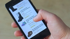 Shopping Online using a smartphone. Baby Shoes: Boots, Slippers, Sneakers Stock Footage