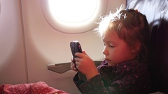 Little child girl passenger watch smart phone cartoons in a plane during flight Stock Footage