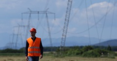 Young Electrician Man Inspection Examine Electric Pylon Walk in Industrial Area Stock Footage