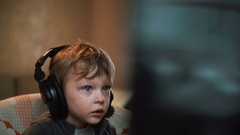 Father straightens big headphones on a little boy who looks attentively Stock Footage