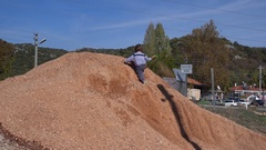 Zoom out Kid playing on soil heap near the road Stock Footage