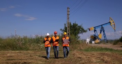Petrochemical Production Engineer Men Team Work Talking Pumping Unit Plans Walk Stock Footage
