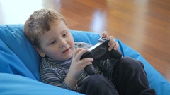 Little cute boy playing a game on the x-box Stock Footage