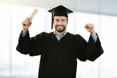 Cheerful smiling graduate wearing gown at graduation ceremony Stock Photos