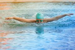 Dynamic and swimmer in cap breathing performing the butterfly stroke Stock Photos
