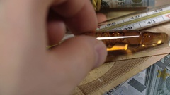 Close-up hand putting medical ampoule about thermometer Stock Footage