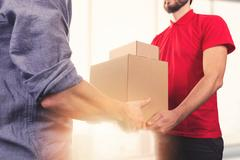 Man accepting a delivery of boxes from delivery service courier Stock Photos