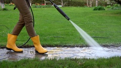 Woman legs with gumboots in garden. washing garden path with water jet. Stock Footage