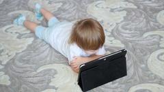 Child looks cartoons on tablet pc on floor Stock Footage