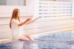 Young Asian woman sitting chill out at swimming pool ,Happy holidays Stock Photos