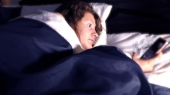A pretty young woman woken from sleep  by her phone ringing. Stock Footage