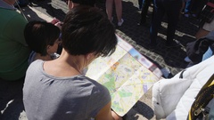 Female tourist looking at map and talking to husband, family vacation planning Stock Footage