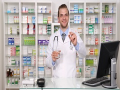 Happy Pharmacist Man Showing Glass of Water and Give Pill Pharmacy Store Concept Stock Footage