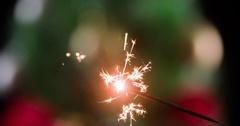 Burning sparkler refocusing decorated Christmas tree 4k close-up video Stock Footage