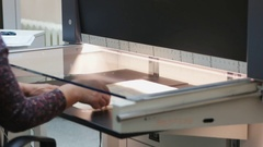Hands putting a sheet of manuscript paper into high resolution scanning device Stock Footage