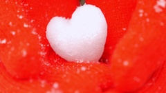 Kid's hands in red gloves holding snow heart while snowing, close up Stock Footage