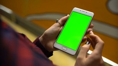 Woman using a mobile phone with green screen, touch and scroll Stock Footage