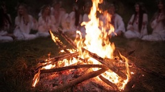 Midsummer night. Young people in Slavic clothes sitting near the bonfire Stock Footage
