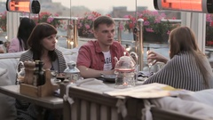 Three friends celebrate a holiday in the restaurant Stock Footage