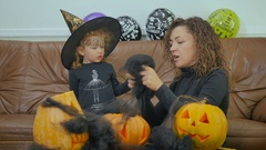 Curly woman and girl play with black spiderweb Stock Footage