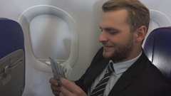 Happy Attractive Businessman Count Us Dollars Cash Earnings in Aircraft Travel Stock Footage