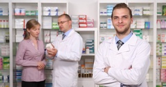 Group of Pharmacists People Working in Pharmacy Shop and Looking Camera Teamwork Stock Footage