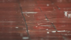 Raindrops falling on floor view from ground level rain with water stream and Stock Footage