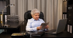 One Senior Retired Female Daily Reading Newspaper Press Info in Home Office Room Stock Footage