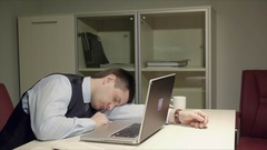 Young, handsome men laying on the desk and sleeping. Then he suddenly waking up Stock Footage