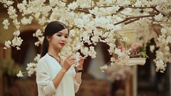 Vietnamese girl with long hair in a white lilac garden Stock Footage