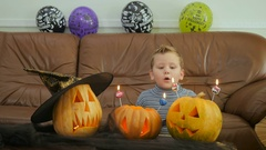 Boyblows candles on scary pumpkins on Halloween Stock Footage