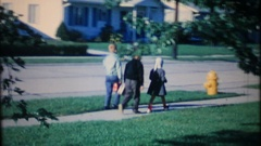 Children leave home and walk to school in suburbia, 3840 vintage film home movie Stock Footage