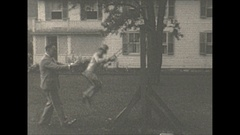 Vintage 16mm film, 1928 man pushing child on swing in backyard Stock Footage