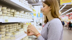 Young woman chooses dairy produce in the store Stock Footage