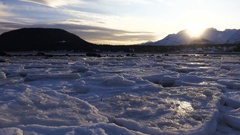 Ice Slabs Scattered and Setting Brilliant Alaskan Sun Over Mountains Stock Footage