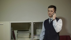 Businessman looking documents in the closet, on the phone Stock Footage
