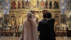 Maid of honor and best man stand behind bride and groom with crowns in hands wed Stock Footage