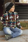 Boy in autumn clothes sitting on the curb Stock Photos