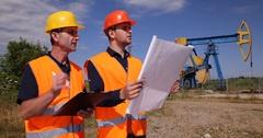 Engineer Technician Men Talking Oil Pump Analyzing Petroleum Installation Plan Stock Footage