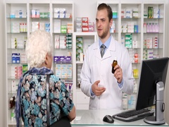 Kindly Pharmacist Man Talking Elderly Old Woman on Medicines Drugs Pharmacy Shop Stock Footage