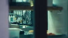 Unrecognizable chief at restaurant kitchen as seen through the window Stock Footage