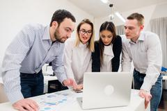 Brainstorm. Group of cheerful business people in smart casual wear looking at Stock Photos