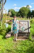Young attractive woman near the village wooden water well in summer sunny day Stock Photos