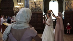 In church orthodox woman bless herself with fingers and bow watching wedding Stock Footage